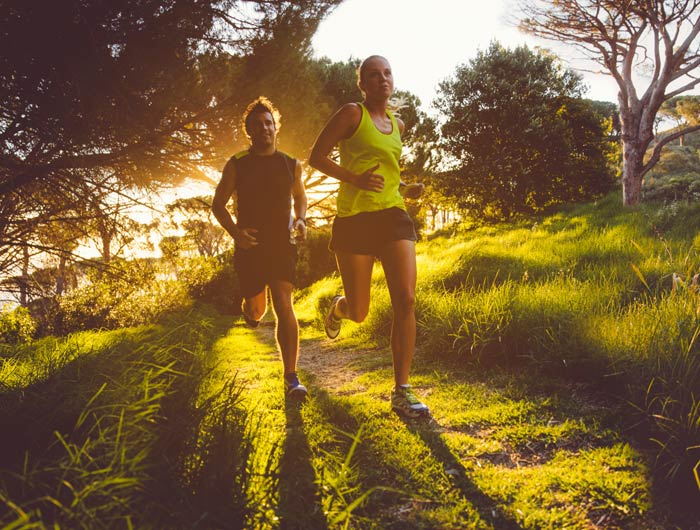 two runners along a grassy path with the sun setting behind them