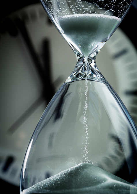 close up of hourglass with clock in the background