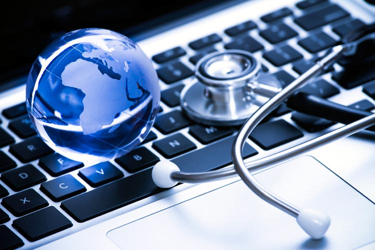 montage of stethoscope and small, transluscent globe on laptop keyboard